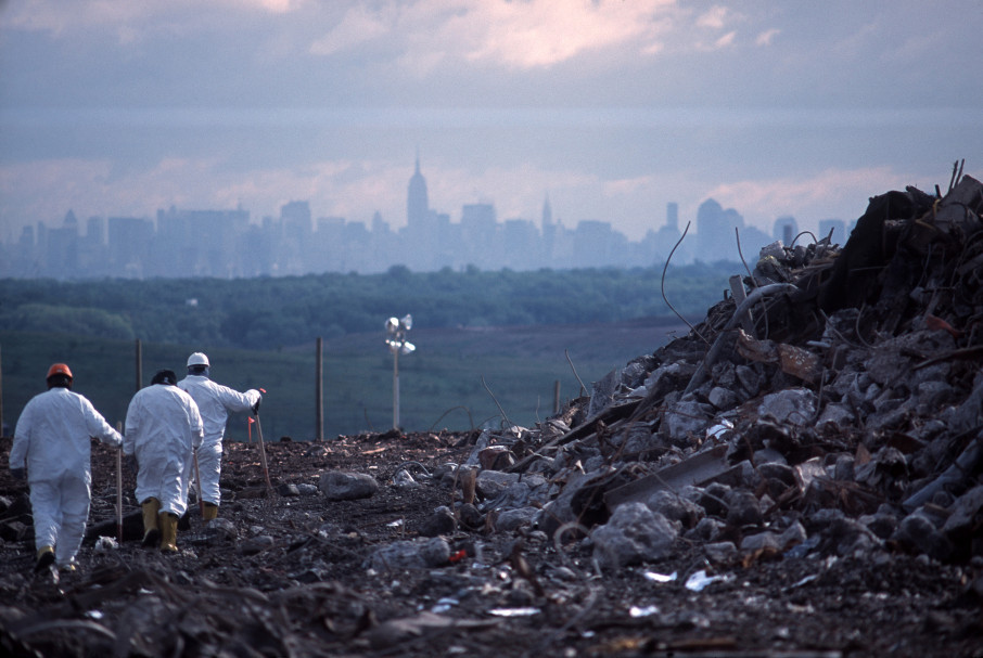 "Investigators walk amongst the remains of WTC debris at Fresh Kills Landfill. The ""New City skyline"" in the background.  2002 Photo by Michael Falco"